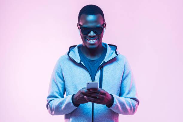 年輕的非洲裔美國人的肖像使用智慧手機聽音樂與耳機 - 霓虹色 個照片及圖片檔