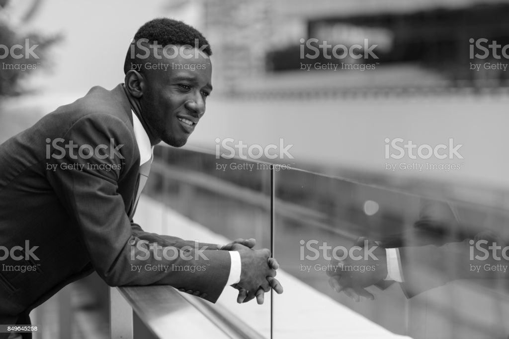 Portrait of young African businessman against view of the city in Bangkok Thailand stock photo