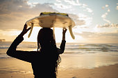 Portrait Of Young African Girl With Surfboard At Pristine Beach at Sunrise in Australia