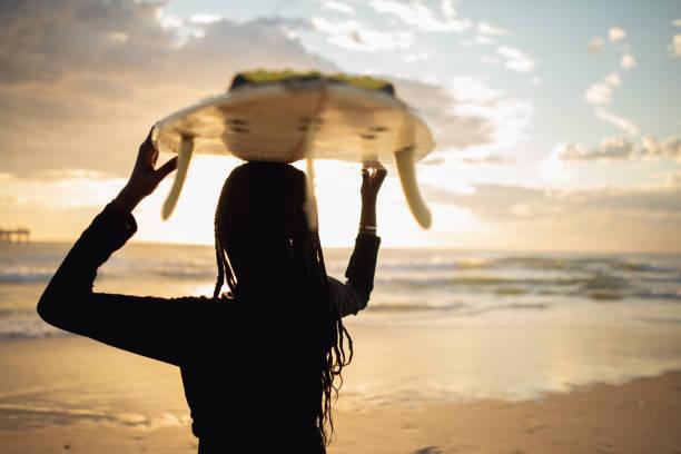 Porträtt av ung afrikansk flicka med surfbräda bildbanksfoto