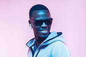 istock Portrait of young african man listening music with wireless earphones, wearing gray hoodie 1093991914