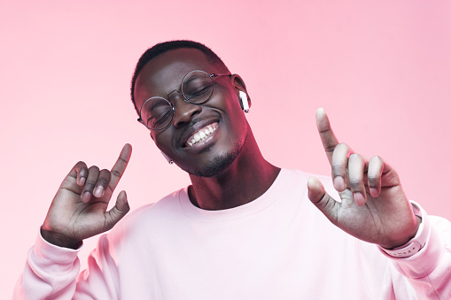 Portrait of young african man listening music with wireless earphones, dancing