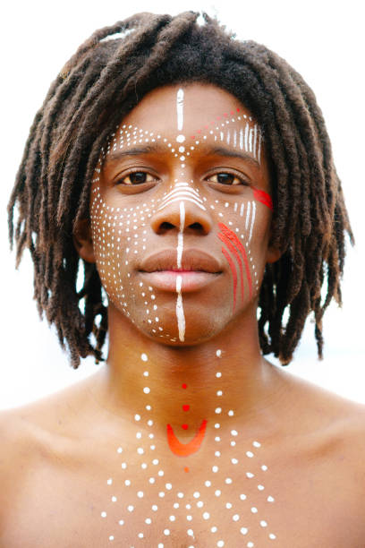 Portrait of young african man with dreadlocks and traditional face paint looking straight into the camera with a serious expression stock photo
