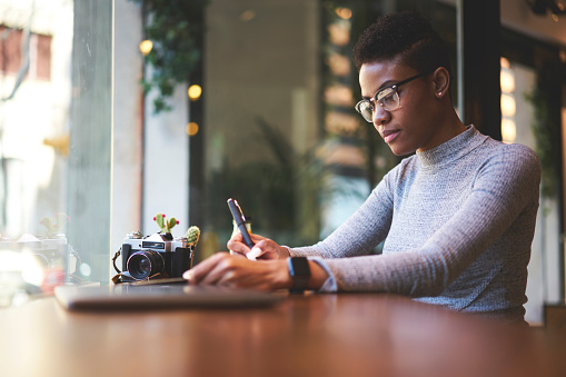 istock Portrait of young afro American skilled executive manager dressed in stylish outfit  conduct business while sitting in cafe waiting for meeting with marketing expert to discuss advertising campaign 905480902