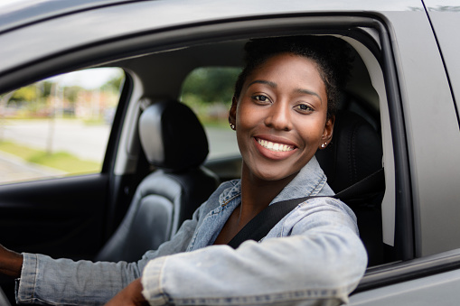 Portrait of young afro woman driving a car