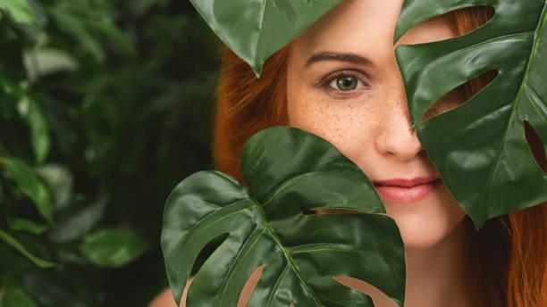porträt der jungen und schönen frau in tropischen blättern - vogue muster stock-fotos und bilder