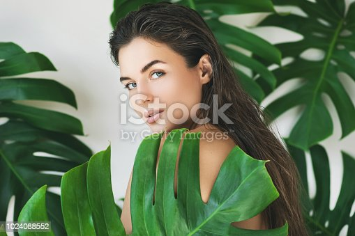 Portrait of young and beautiful woman with perfect smooth skin in tropical leaves. Concept of natural cosmetics and skincare.