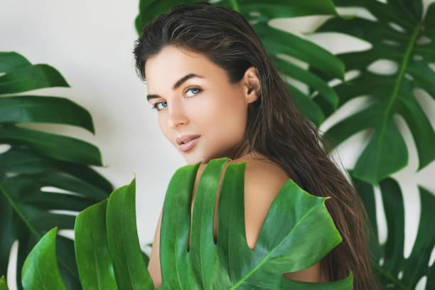 熱帶樹葉上完美光滑皮膚的年輕美麗女子肖像 - 時裝模特兒 個照片及圖片檔