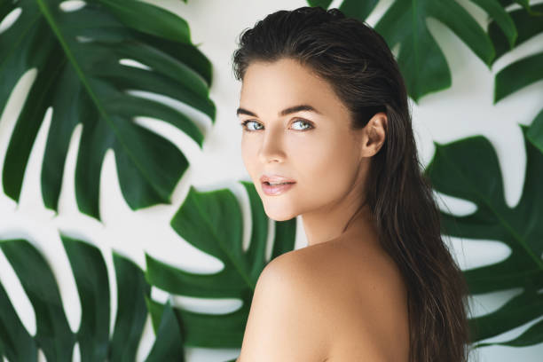 Portrait of young and beautiful woman with perfect smooth skin in tropical leaves stock photo