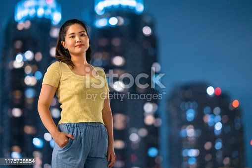 A portrait of a young and confident woman at night in front of office buildings.
