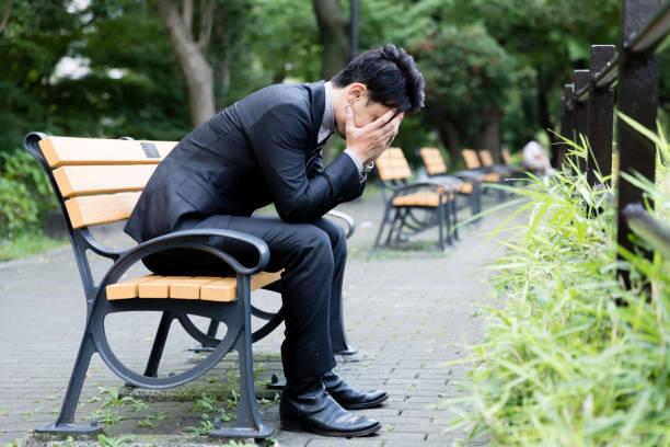 公園で若いアジア系のビジネスマンの肖像画 - 絶望 ストックフォトと画像