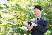 公園でスマート フォンを使用して若いアジア系のビジネスマンの肖像画