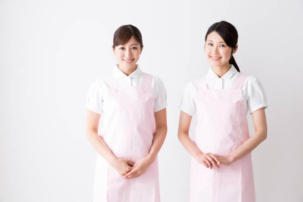 白地に分離された若いアジア介護ヘルパーの肖像画 - 介護士 ストックフォトと画像