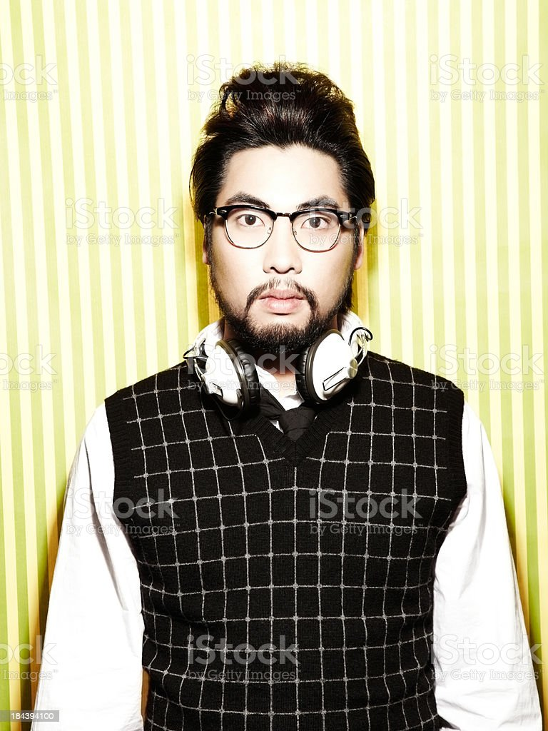 Portrait of young Asian DJ against striped background royalty-free stock photo