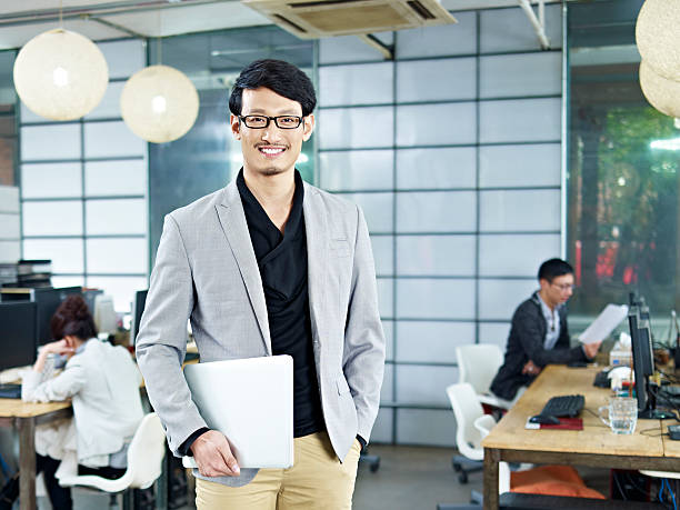 portrait of young asian entrepreneur young asian entrepreneur standing in office with laptop computer under arm. japanese ethnicity stock pictures, royalty-free photos & images