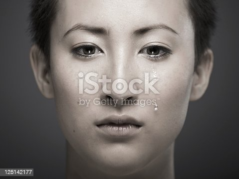 istock Portrait of young Asian girl with tear rolling down cheek 125142177