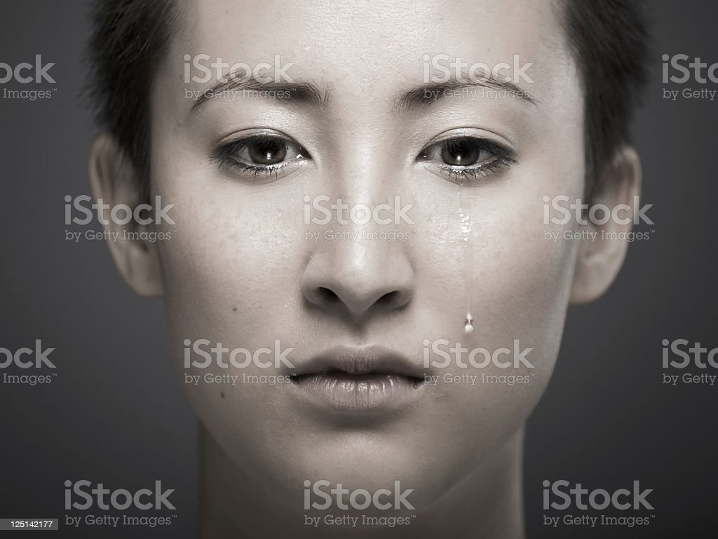 Portrait of young Asian girl with tear rolling down cheek stock photo