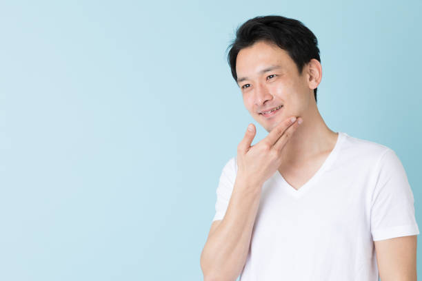 portrait of young asian man isolated on blue background portrait of young asian man isolated on blue background hair stubble stock pictures, royalty-free photos & images