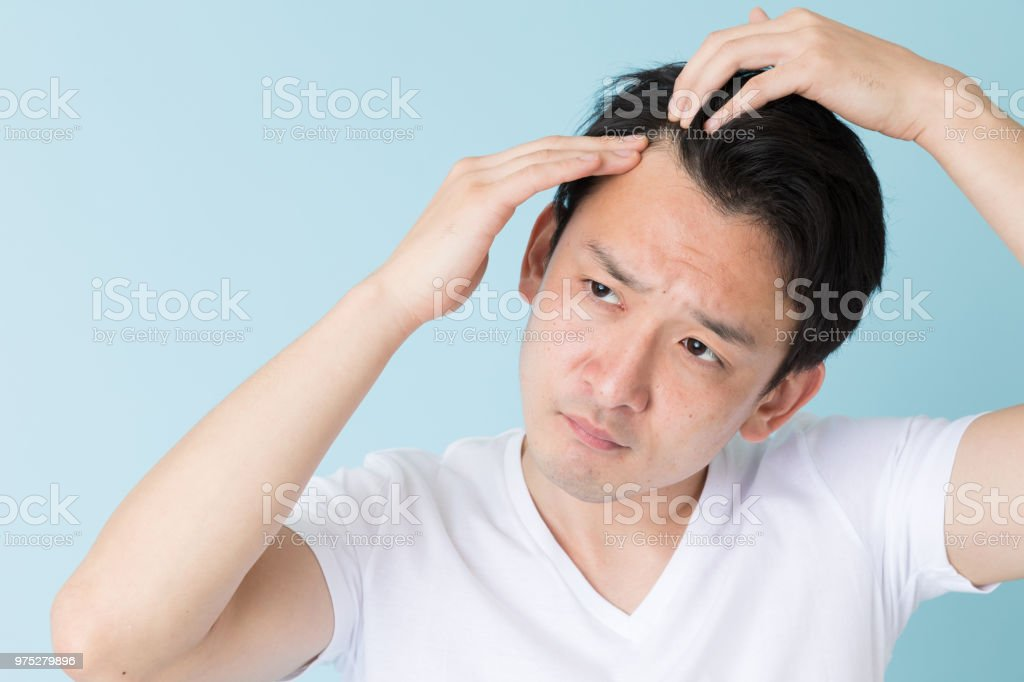 portrait of young asian man isolated on blue background stock photo