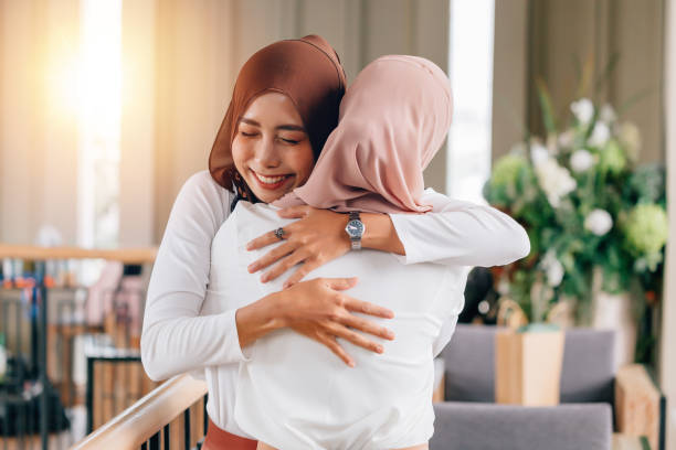 portrait of young asian muslim women in happy smile with hijab or head scarf hugs each other indoors - религиозная одежда стоковые фото и изображения