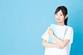 青の背景に分離された若いアジアの看護師の肖像