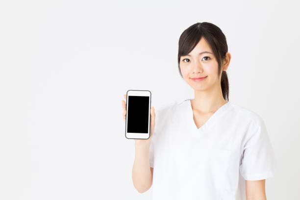 若いアジアの看護師が白い背景で隔離の肖像画 ストックフォト