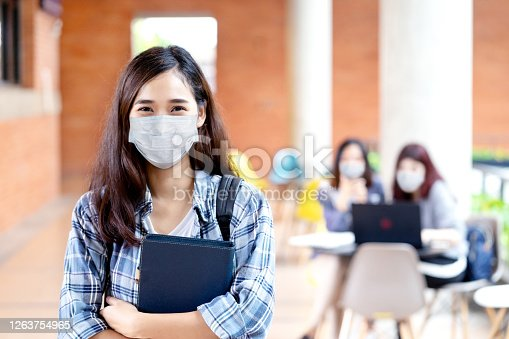 istock Portrait of young asian student wear mask looking at camera holding notebook or tablet in arm in concept come back or return to school, school reopening and unlock after covid or coronavirus outbreak. 1263754965