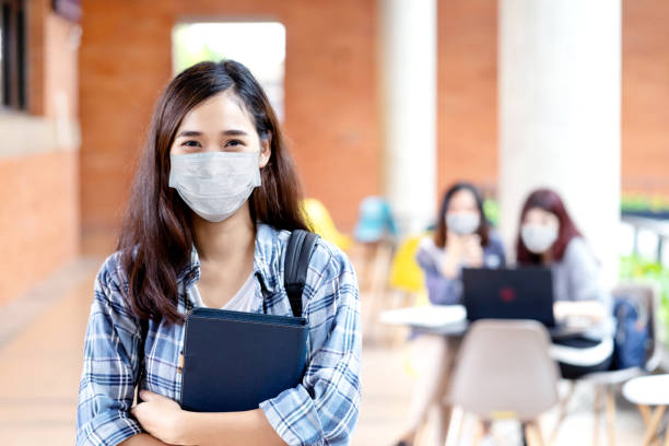 Portrait of young asian student wear mask looking at camera holding notebook or tablet in arm in concept come back or return to school, school reopening and unlock after covid or coronavirus outbreak. stock photo