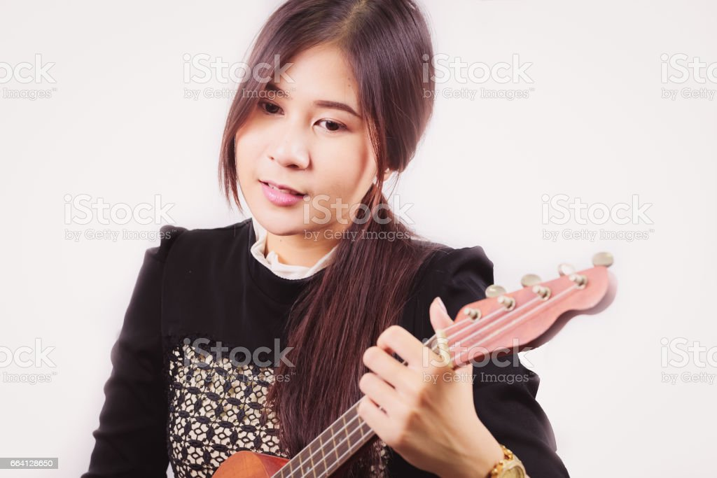 Portrait of young Asian woman enjoys playing guitar, isolated on white background. foto stock royalty-free