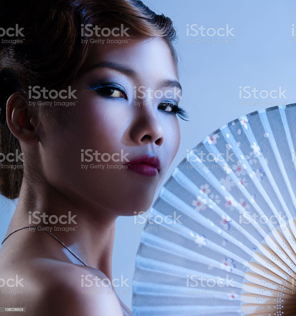 Portrait of Young Asian Woman Holding Fan royalty-free stock photo