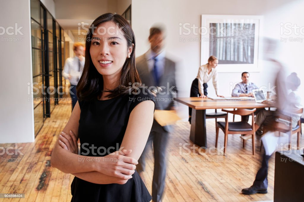 Portrait of young Asian woman in a busy modern workplace stock photo
