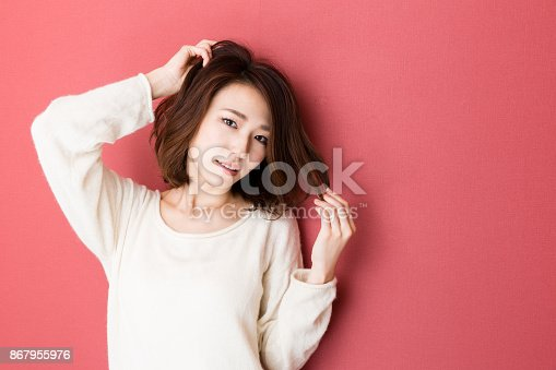 istock portrait of young asian woman isolated on red background 867955976