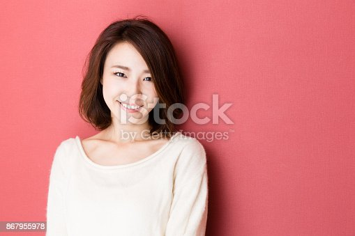 istock portrait of young asian woman isolated on red background 867955978