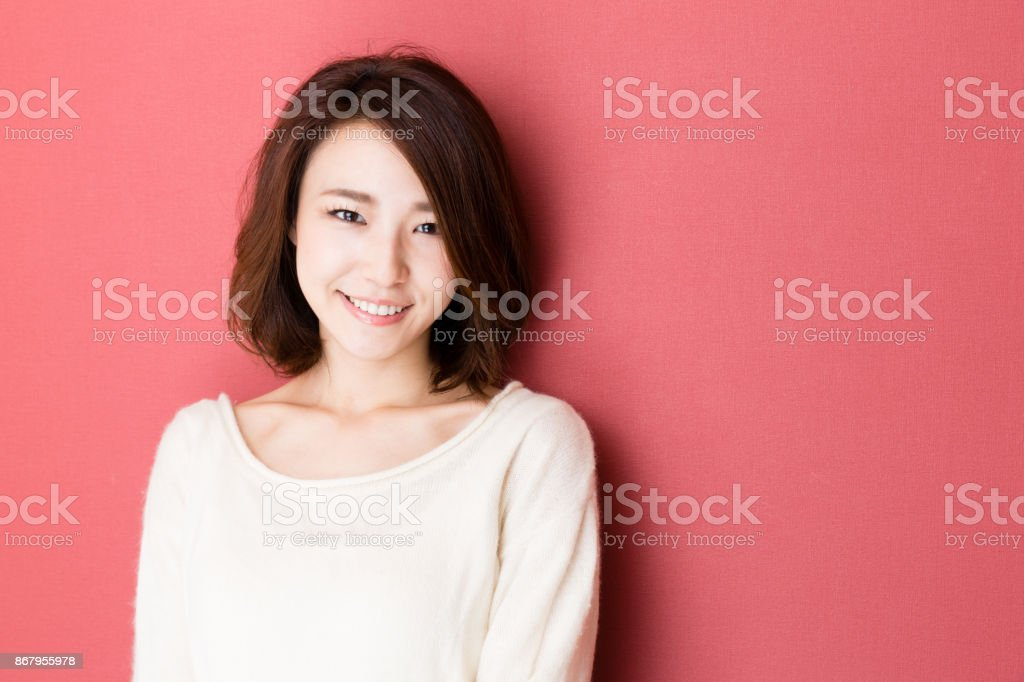 portrait of young asian woman isolated on red background stock photo