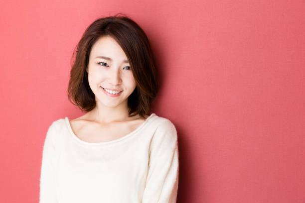 赤の背景に分離された若いアジア女性の肖像画 - 東洋民族 ストックフォトと画像