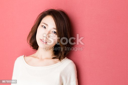 istock portrait of young asian woman isolated on red background 867955980