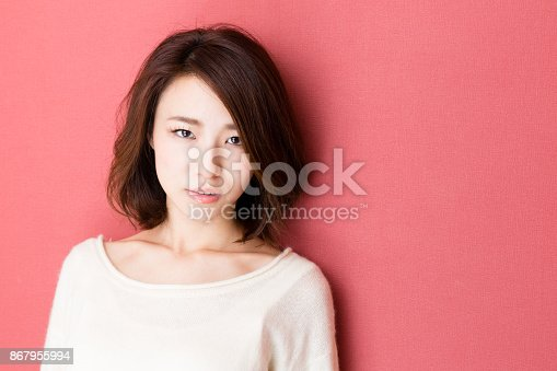 istock portrait of young asian woman isolated on red background 867955994