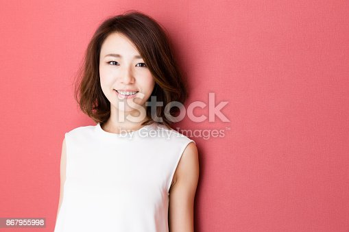 istock portrait of young asian woman isolated on red background 867955998