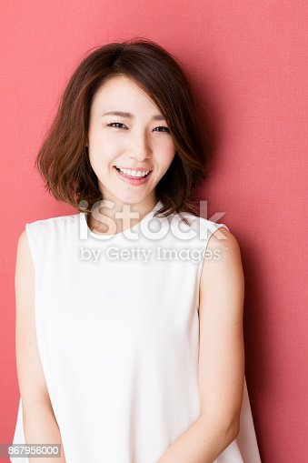 istock portrait of young asian woman isolated on red background 867956000