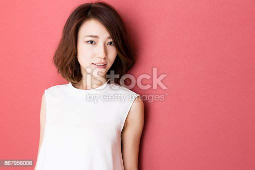 istock portrait of young asian woman isolated on red background 867956006