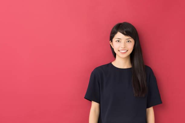 赤の背景に分離された若いアジア女性の肖像画 ストックフォト