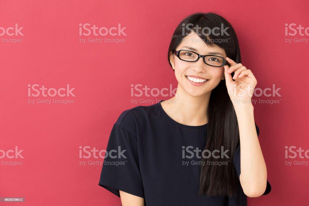 赤の背景に分離された若いアジア女性の肖像画 - 1人のロイヤリティフリーストックフォト