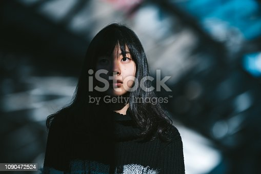 A portrait of a young Asian woman while half of her face is lit by the sun and the other half is in the shadow.