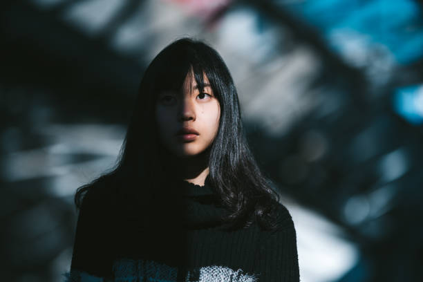 Portrait of young Asian woman A portrait of a young Asian woman while half of her face is lit by the sun and the other half is in the shadow. apprehension stock pictures, royalty-free photos & images