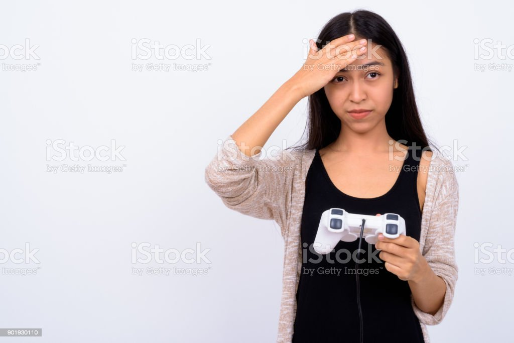 Portrait Of Young Asian Woman Playing Games With Game Controller Against White Background stock photo
