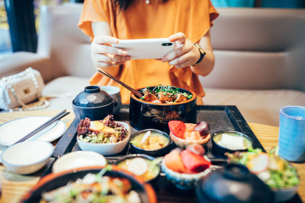 Portrait of young Asian woman taking picture of her fresh Japanese food with mobile phone in restaurant. stock photo