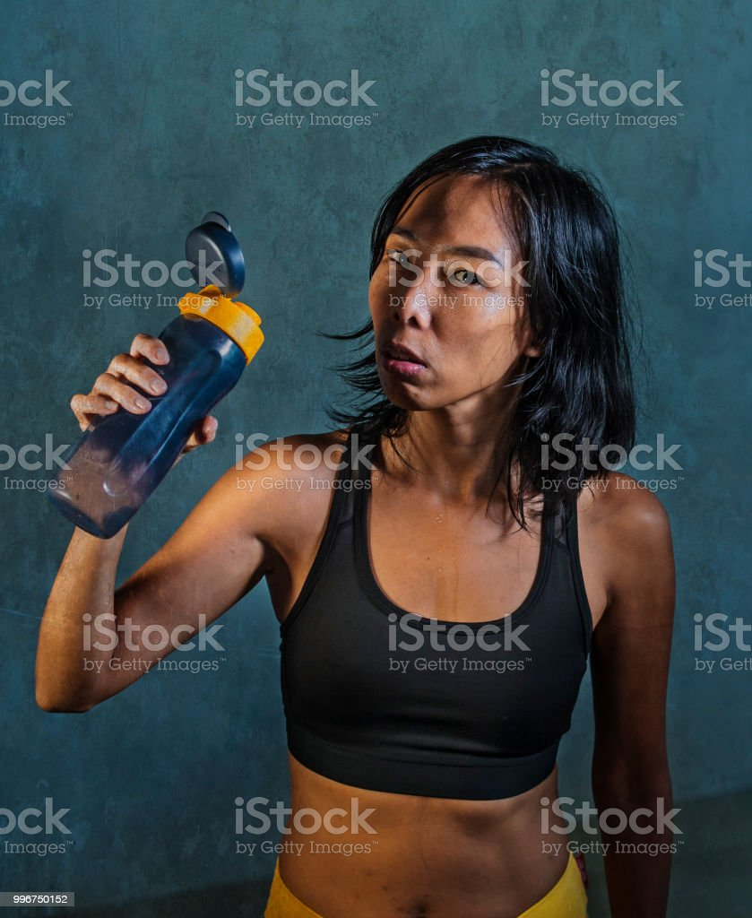 4e4fc245c3031 Portrait Of Young Athletic And Fit Asian Korean Woman In Fitness Top  Holding Drinking Water Bottle Posing Cool In Bad Girl Defiant Attitude  Isolated On Dark ...