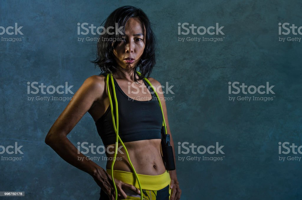 portrait of young athletic and fit Asian Korean woman in fitness top holding skipping rope posing cool in bad girl defiant attitude isolated on dark background in gym sport workout concept stock photo