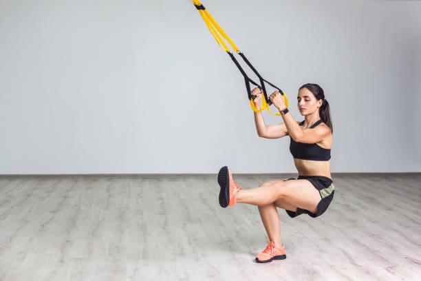 porträtt av ung atletisk kvinna i sportkläder gör squat övning, träning ben och glutes muskulös med fitness remmar i gymmet. - remmar godis bildbanksfoton och bilder
