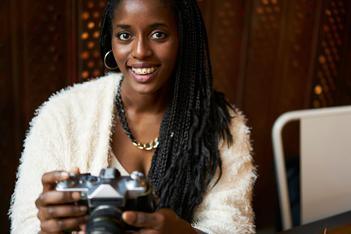 istock Portrait of young attractive afro american female professional photographer testing usability of old vintage camera, smiling teenager in casual clothes spending leisure time on hobby in cafe indoors 908018308